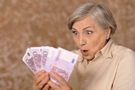 woman holding money: Portrait of an aged woman holding money Stock Photo