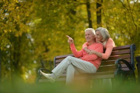 Happy elderly couple sitting on bench in autumn park Standard-Bild