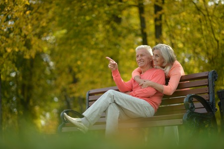 fashionable couple: Happy elderly couple sitting on bench in autumn park Stock Photo