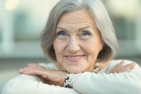 Portret van een gelukkige senior vrouw in de herfst park Stockfoto