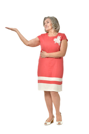 full length portrait: Full length portrait of senior woman pointing on white background
