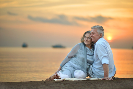 old man portrait: Portrait of a senior couple at sea at sunset Stock Photo
