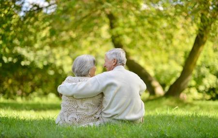 Happy elderly couple sitting in autumn park