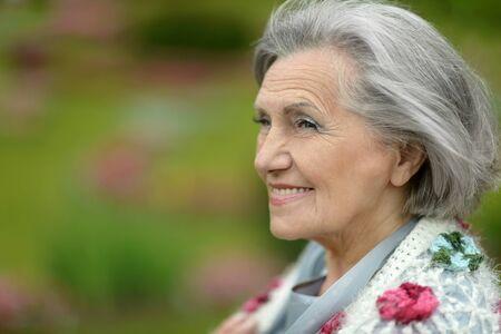 elder care: Senior happy woman on walk in summer park