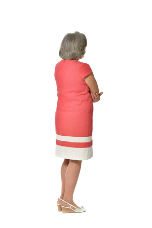 Full length Portret van senior vrouw in rode jurk, achteraanzicht op een witte achtergrond Stockfoto