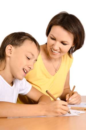 two minds: Mother and son are drawing together with pencils at table