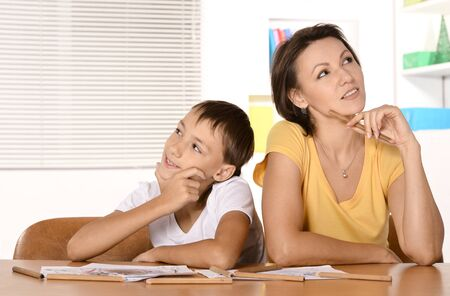 two minds: Mother and son are drawing together with pencils Stock Photo