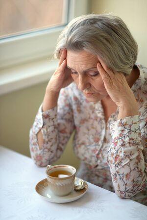 sad old woman: Portrait of a sad old woman drinking tea