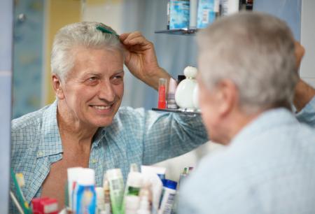 combing hair: Senior man combing hair in the bathroom