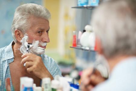 greying: Portrait of a senior man shaving in bath