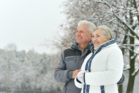 family health: Portrait of elderly couple having fun outdoors in winter forest