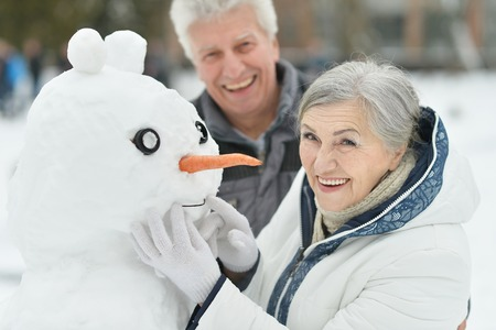 making fun: Portrait of elderly couple making snowman and shows thumbs up in winter