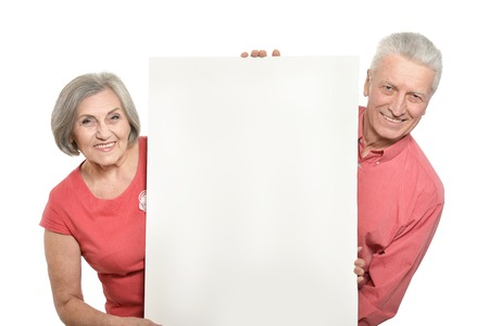 ad: Old age couple holding blank banner ad against white background Stock Photo