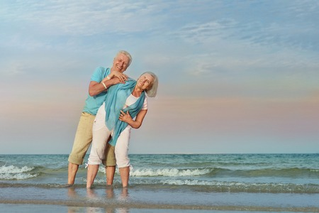 Happy Mature couple enjoy fresh air on beach Foto de archivo