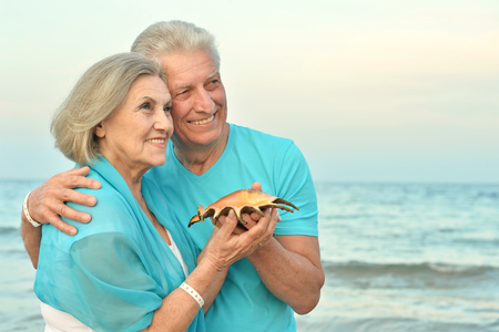 aire puro: Happy Mature couple enjoy fresh air on beach with seashell