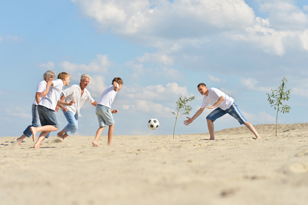 mother and teen daughter: Big Family playing football on a beach in summer day