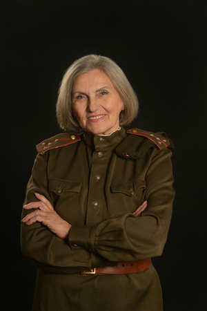 comrade: Elderly female soldier on a black background Stock Photo