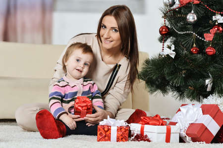 adult child: Happy mother with a little boy near a Christmas tree. new year gifts