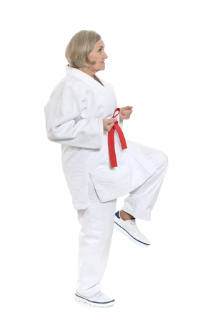 karate female: Senior woman in karate pose on white background