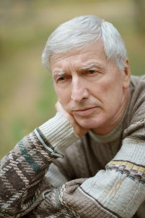 unhappy people: Portrait of thoughtful elderly man on yellow autumn background