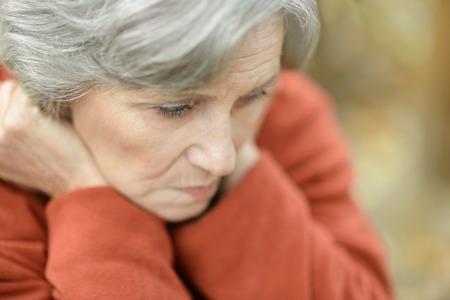 Mooie trieste oude vrouw op de herfst achtergrond
