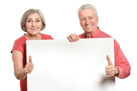 Old age couple holding blank banner ad against white background Foto de archivo