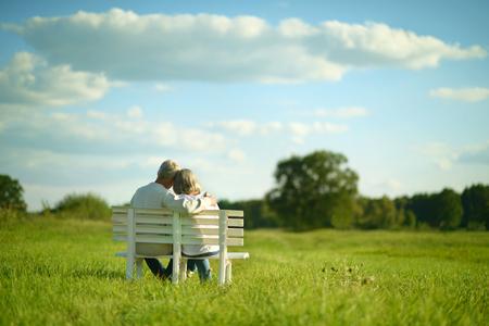 Amusing senior paar zittend op een bankje in het park