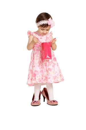 big shoes: Beautiful little girl in a pink dress and big shoes with shopping bag stands on a white background Stock Photo