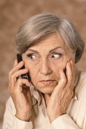 Portrait of worried elderly woman speaking on mobile against brown background Stock Photo
