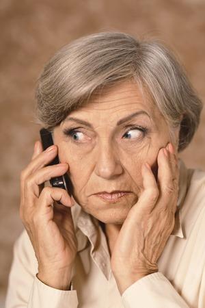 elder care: Portrait of worried elderly woman speaking on mobile against brown background Stock Photo