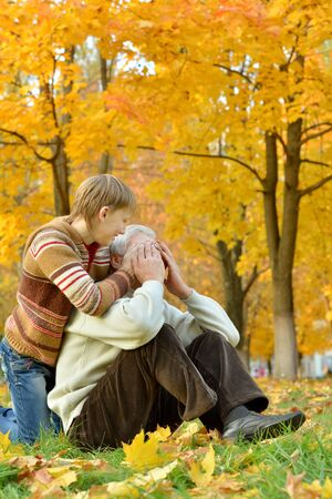 closes eyes: Grandfather with boy resting in autumn park,boy closes grandfathers eyes