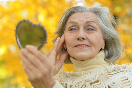 aging woman: Portrait of a elderly woman with mirror in autumn Stock Photo