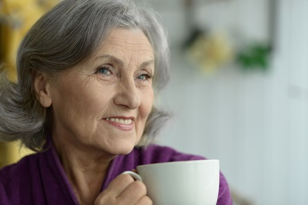 one senior: Attractive elderly woman with cup of coffee