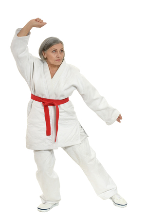 martial arts woman: Senior woman in karate pose on white background