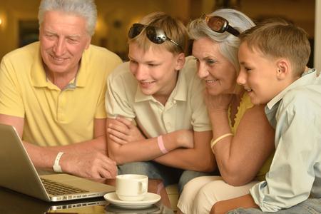 abuelos: Retrato de una joven feliz niños con los abuelos y portátil