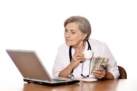 doctor with dollars: Senior doctor sitting at table with laptop and holding dollars Stock Photo