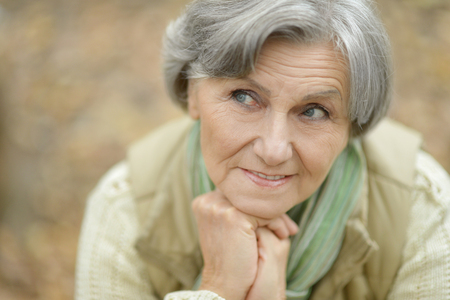 happy seniors: Happy elderly woman enjoying in autumn park