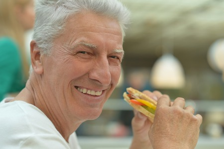 eating fast food: Portrait of a happy elderly man with fast food Stock Photo
