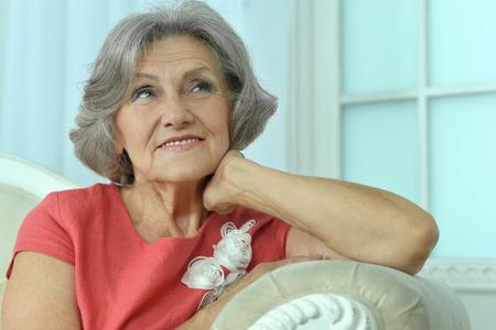 mature woman sitting: Mature woman sitting on a vintage sofa Stock Photo