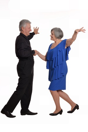 Elegant elderly couple dancing on a white background