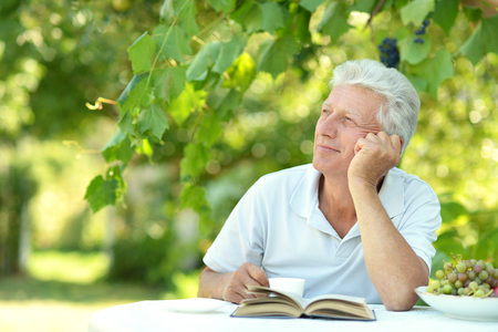mature men: Handsome older man sitting at a table at home on the veranda with book Stock Photo