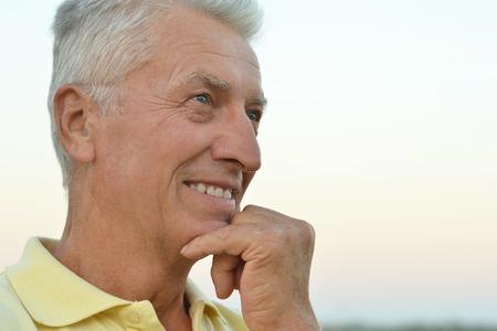 hombres maduros: Retrato de un hombre mayor que piensa en algo al aire libre