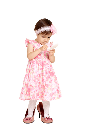 big shoes: Beautiful little girl in a pink dress and big shoes stands on a white background Stock Photo