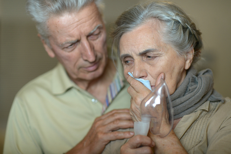 inhalation: Portrait of elderly man and woman with flu inhalation