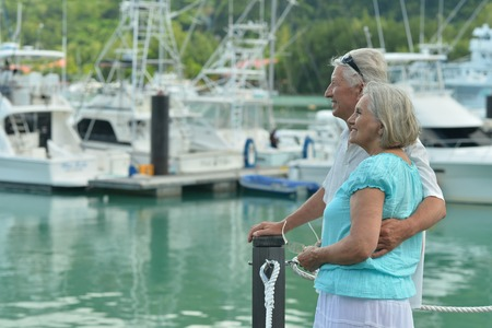 mature people: Happy cute senior couple on the pier with  yachts Stock Photo