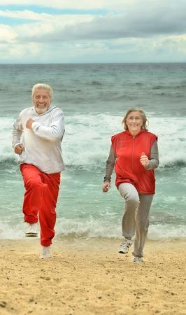 dult: Happy elderly couple running  on a beach Stock Photo