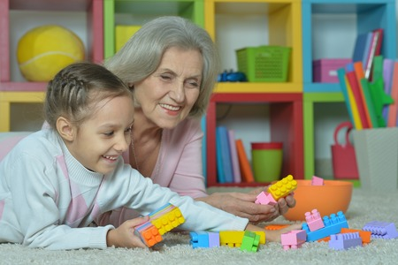 grandkid: Portrait of a happy grandmother with granddaughter playing together Stock Photo