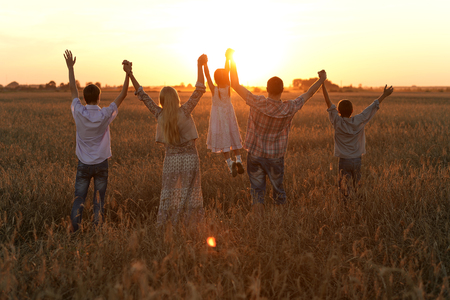 Family holding hands looking at sunset in field Foto de archivo