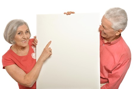 Two elderly posing with board on white Foto de archivo