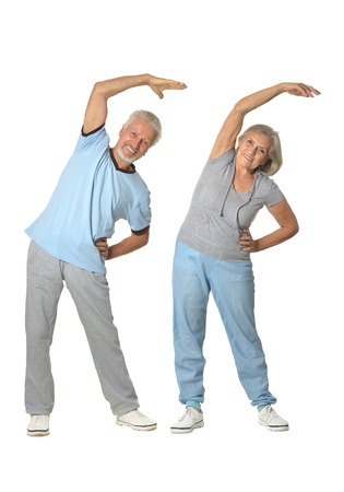 Portrait of Senior Couple Exercising On White Background Foto de archivo